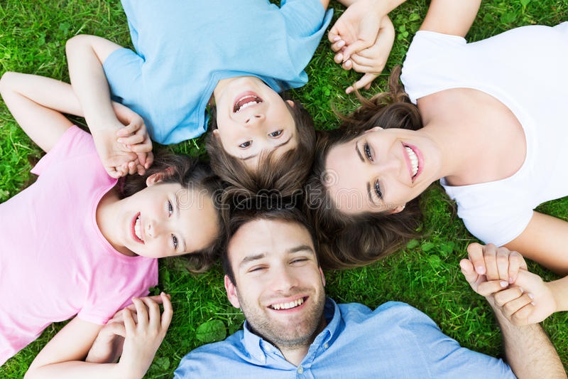 Família que encontra-se no sorriso da grama imagens de stock