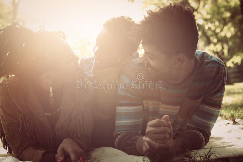 família que encontra-se para baixo no parque e que tem a conversação fotografia de stock