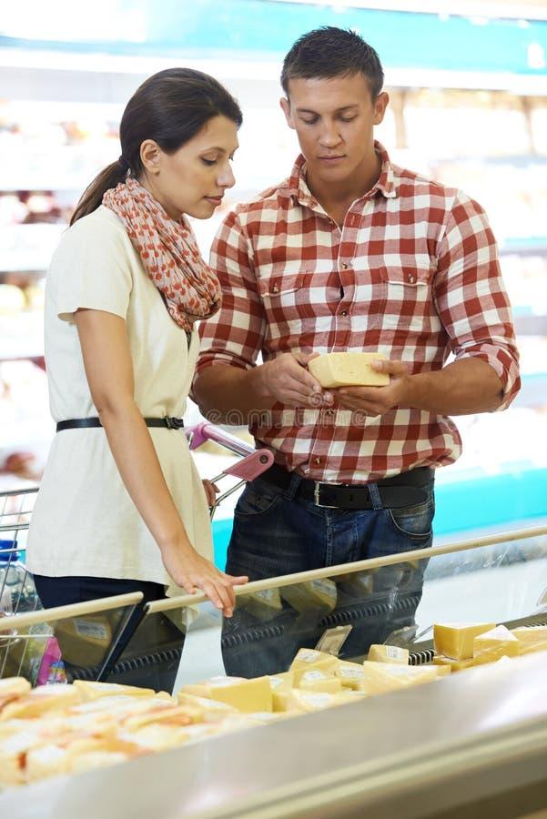 Família que escolhe o alimento na compra no supermercado imagem de stock