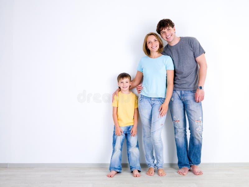 Família que está junto perto da parede vazia imagens de stock royalty free