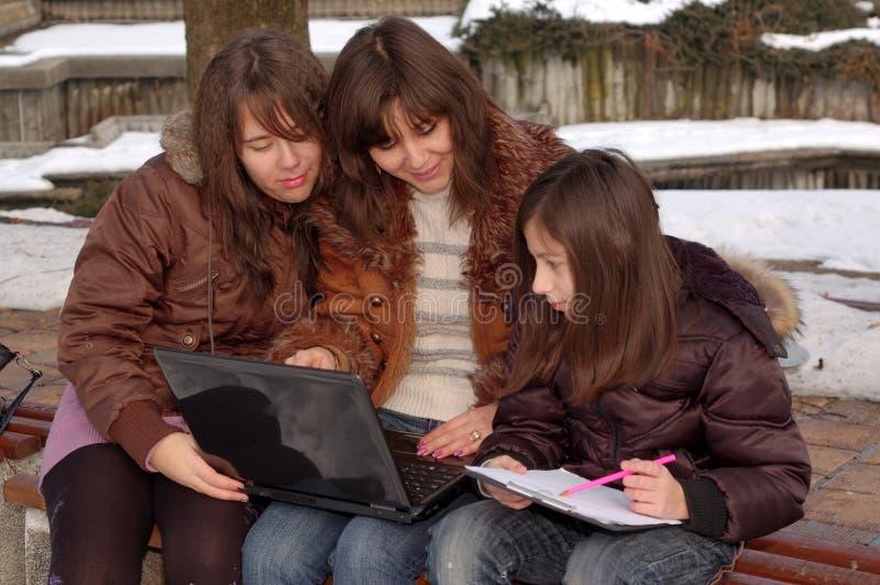Família que estuda o portátil imagem de stock