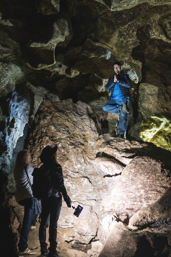 Família que explora a caverna enorme Os viajantes da aventura vestiram o chapéu de vaqueiro e a trouxa, grupo de pessoas férias v fotos de stock