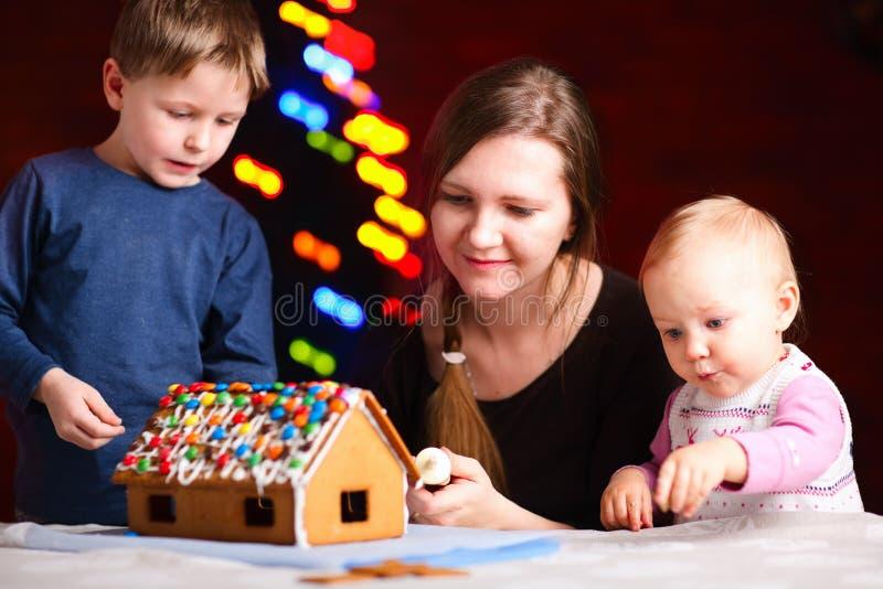 Família que faz a casa de pão-de-espécie fotos de stock