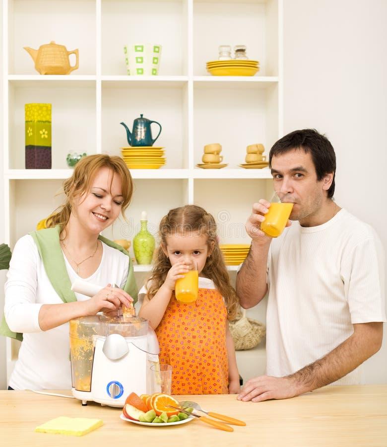 Família que faz e que bebe o suco de fruta fresca imagens de stock