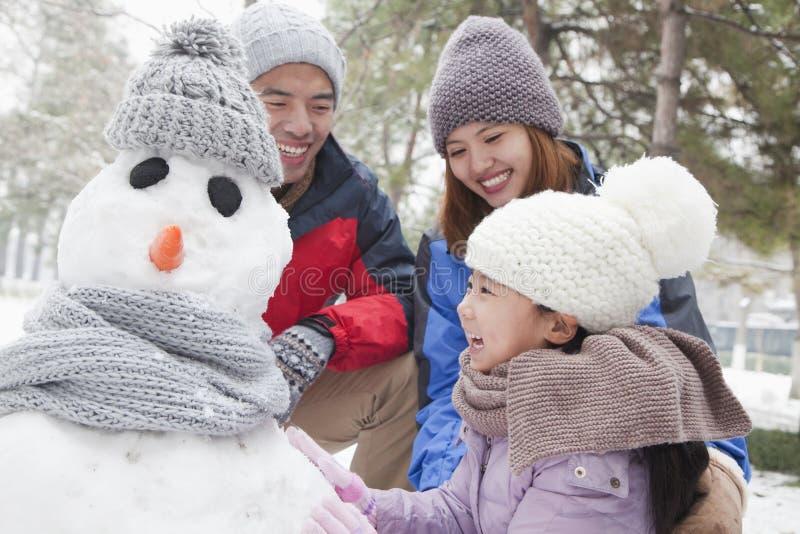 Família que faz o boneco de neve em um parque no inverno fotos de stock royalty free