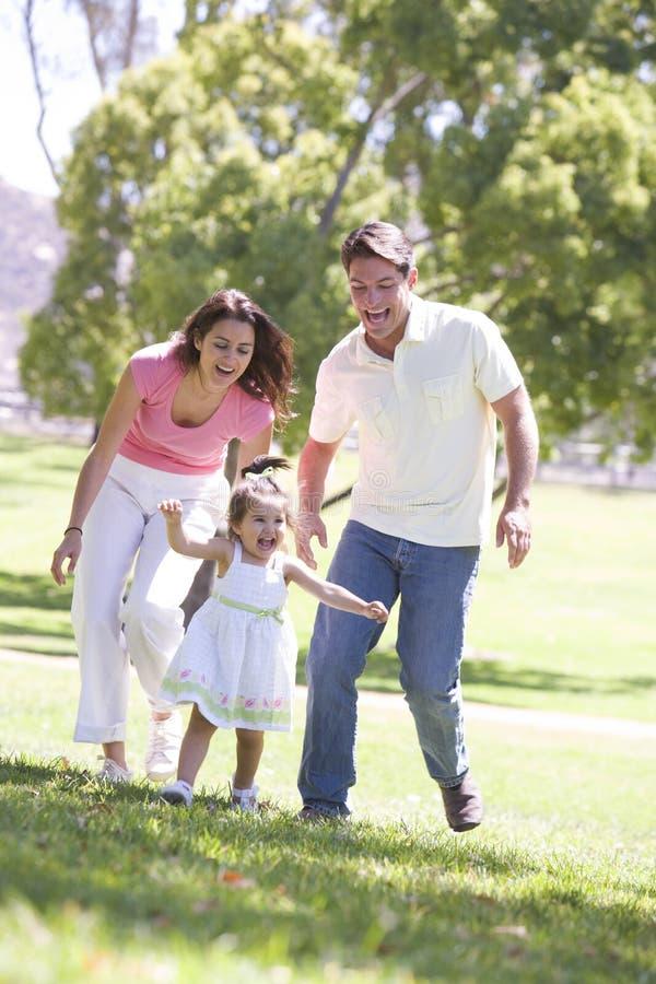 Família que funciona ao ar livre o sorriso imagem de stock