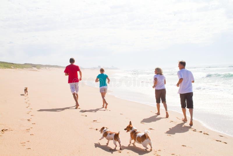 Família que funciona na praia fotos de stock