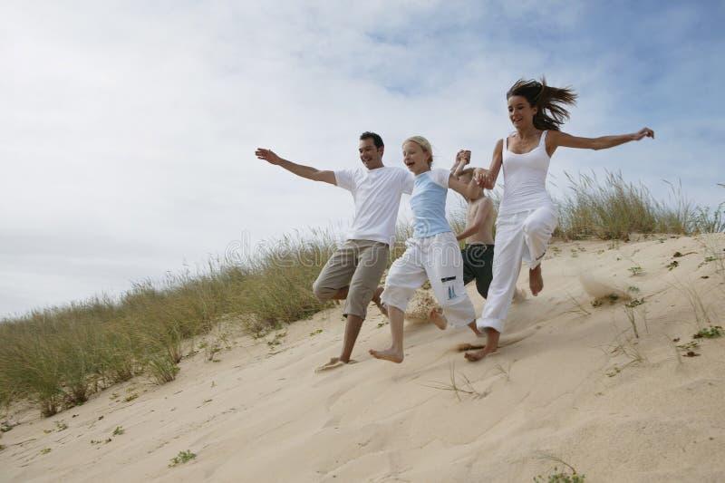 Família que funciona na praia fotografia de stock