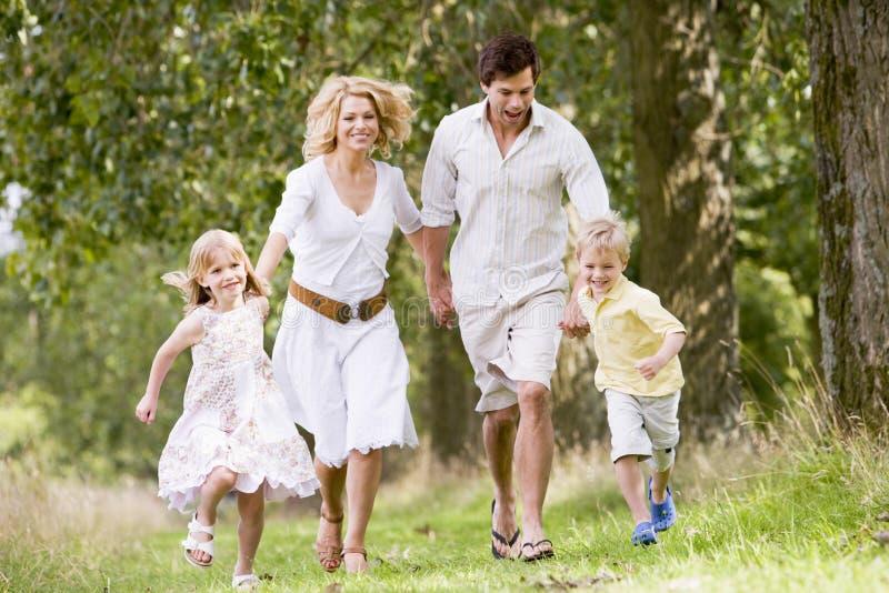 Família que funciona no sorriso das mãos da terra arrendada do trajeto imagem de stock