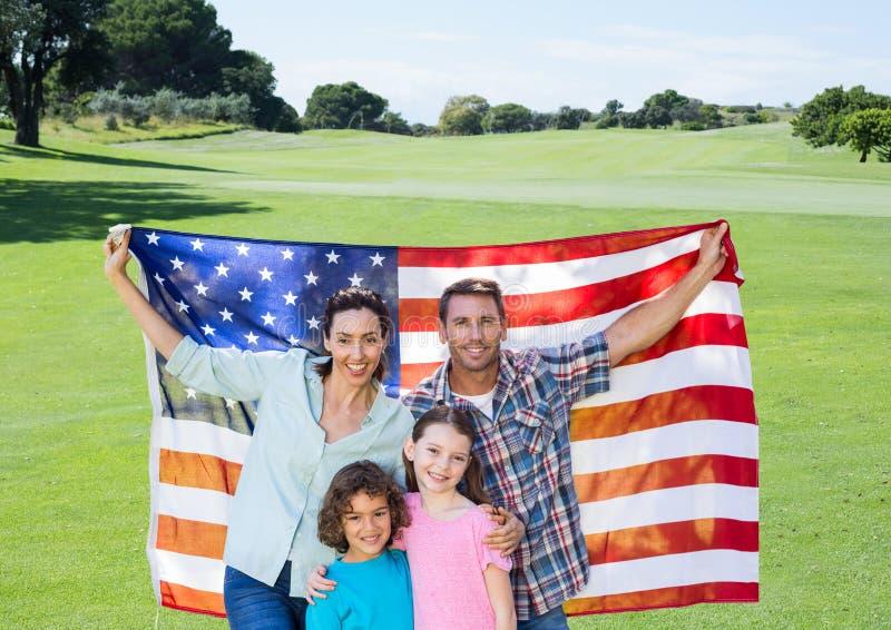 Família que guarda uma bandeira americana no parque imagem de stock royalty free