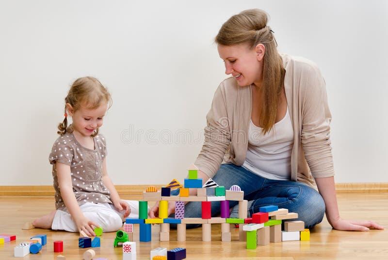 Família que joga com blocos de apartamentos imagem de stock