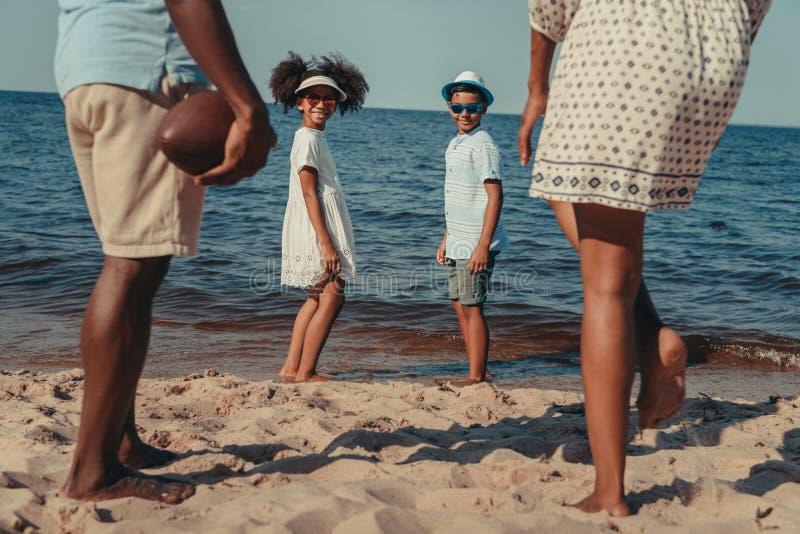 família que joga com a bola na praia foto de stock