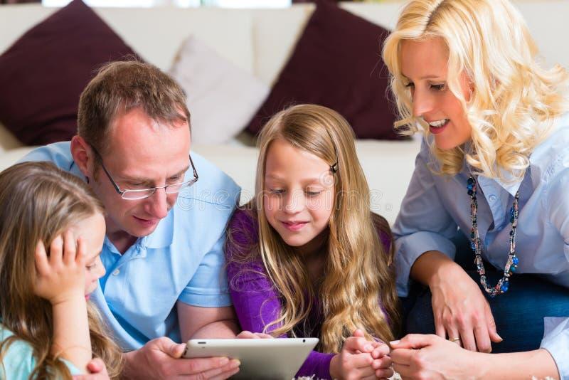 Família que joga com computador da tabuleta em casa