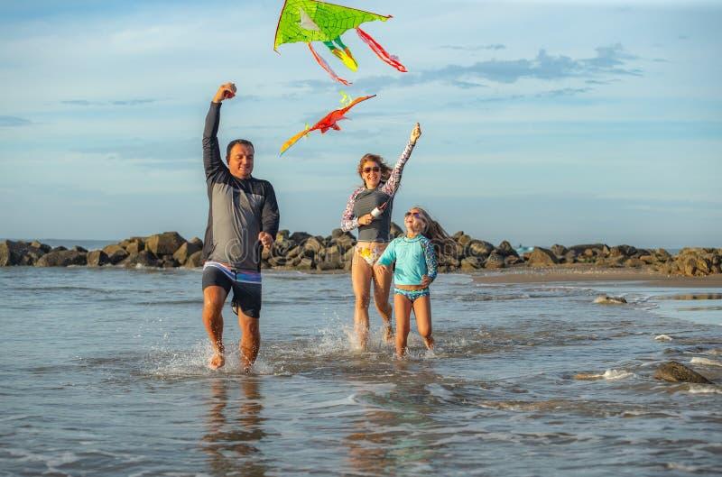 Família que joga com papagaio em umas férias de verão imagem de stock