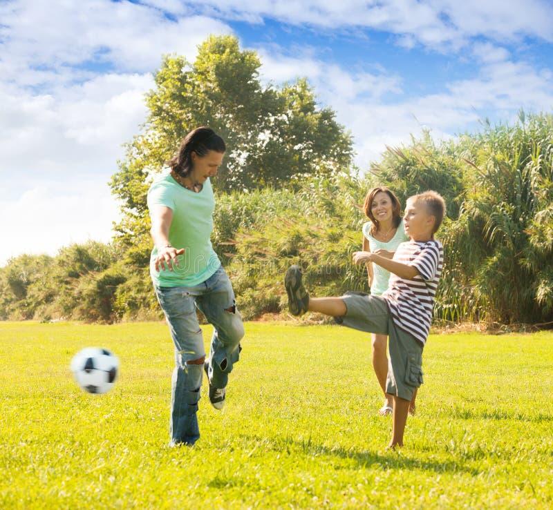 Família que joga junto com bola de futebol imagem de stock