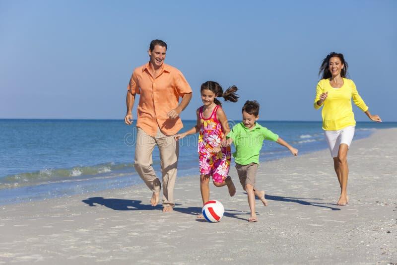 Família que joga o futebol do futebol na praia fotografia de stock royalty free