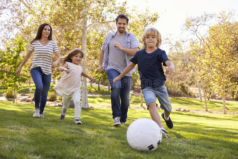 Família que joga o futebol no parque junto foto de stock