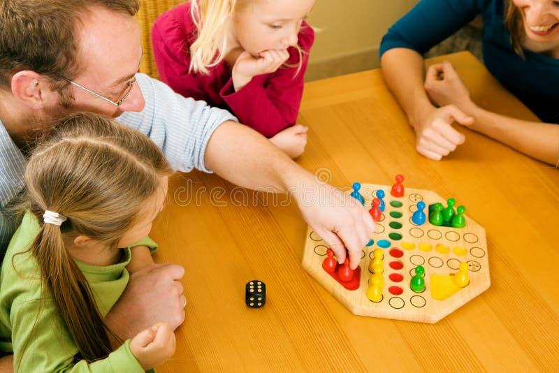 Família que joga um jogo de mesa fotografia de stock