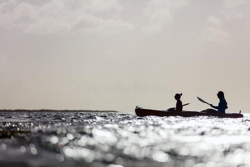 Família que kayaking no por do sol imagem de stock