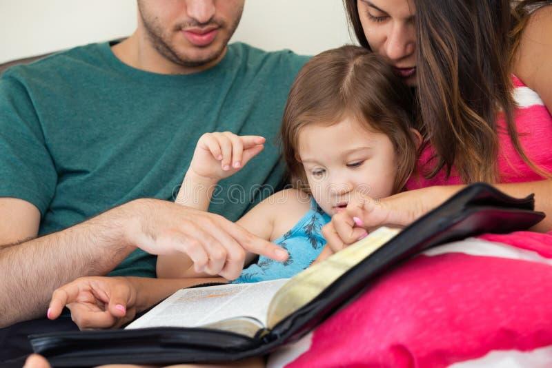 Família que lê a Bíblia junto imagem de stock