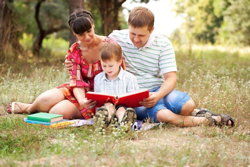 Família que lê junto. Férias de verão imagem de stock royalty free