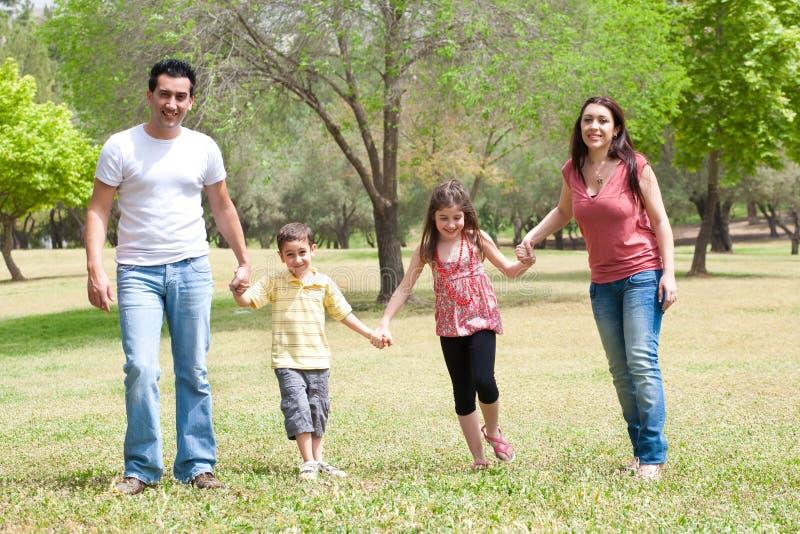Família que levanta à câmera no parque fotos de stock royalty free