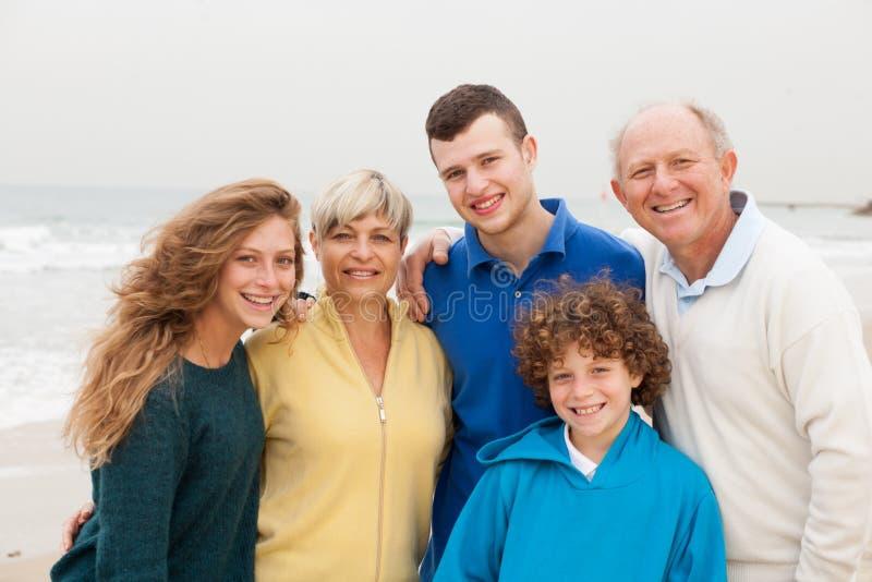 Família que levanta no fundo da praia fotos de stock