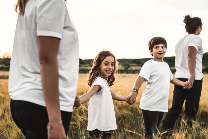 Família que mantém as mãos no campo felizes imagem de stock