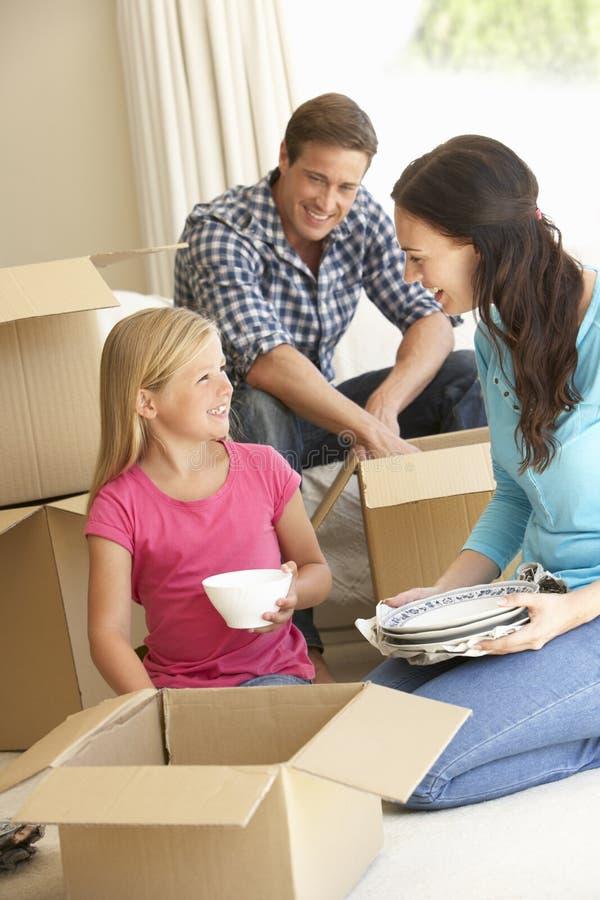 Família que move-se na casa nova cercada por caixas de embalagem imagem de stock royalty free