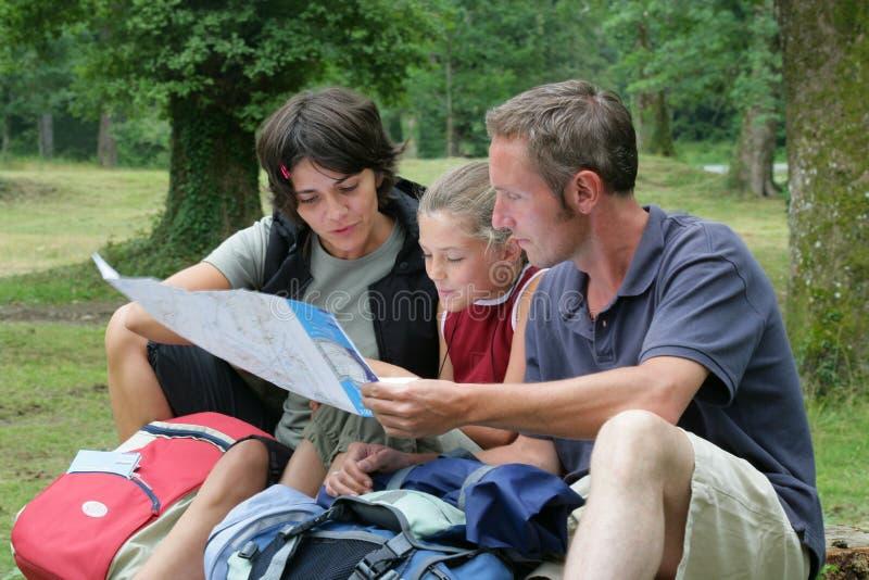 Família que olha de caminhada o mapa imagens de stock