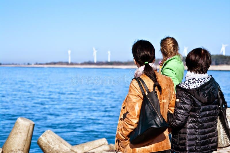 Família que olha o mar imagem de stock