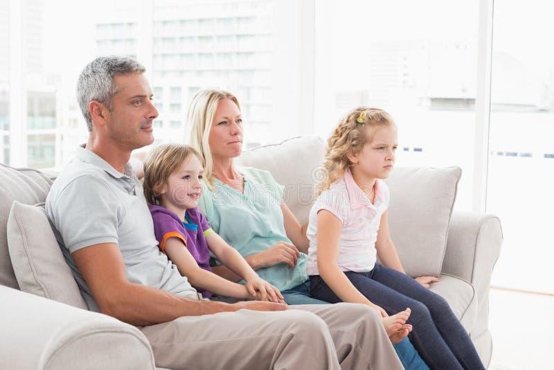 Família que olha a tevê ao sentar-se no sofá imagem de stock