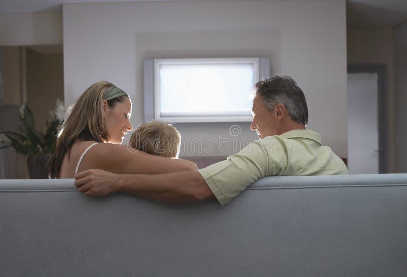 Família que olha a tevê em casa imagens de stock royalty free