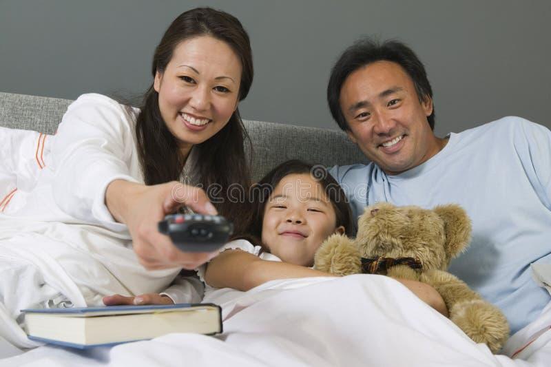 Família que olha a tevê junto na cama imagem de stock