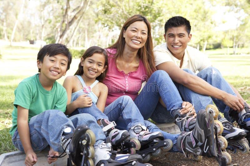 Família que põr sobre na linha patins no parque fotografia de stock