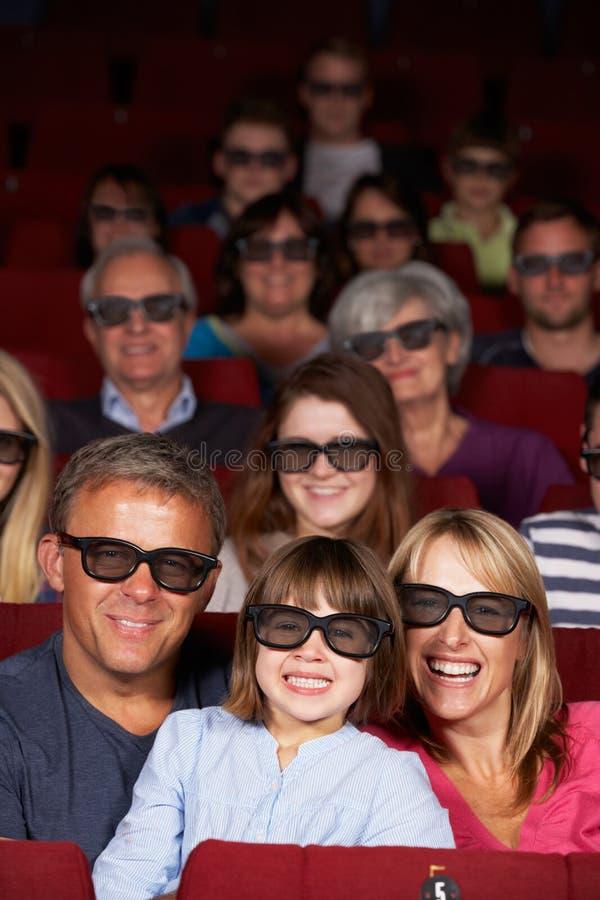 Família que presta atenção à película 3D no cinema foto de stock