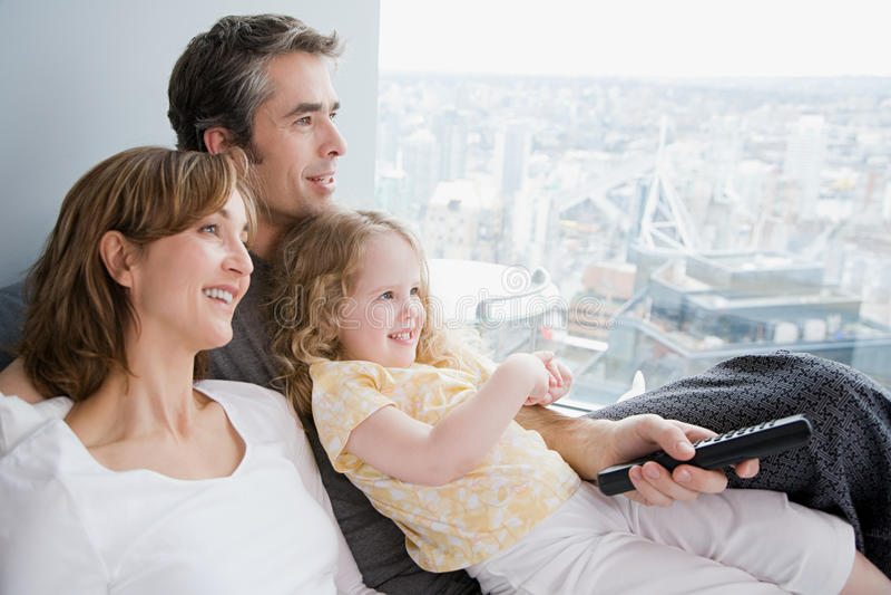 Família que presta atenção à tevê foto de stock royalty free