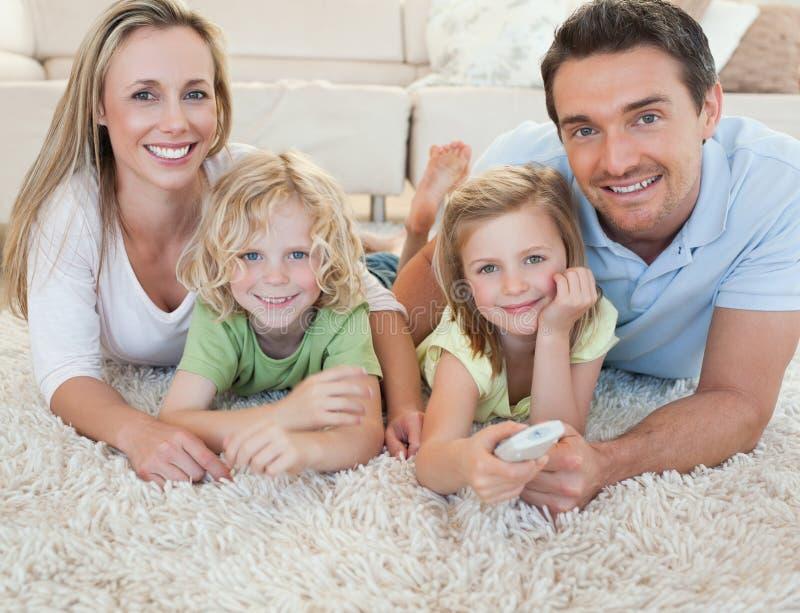 Família que presta atenção à tevê no assoalho foto de stock