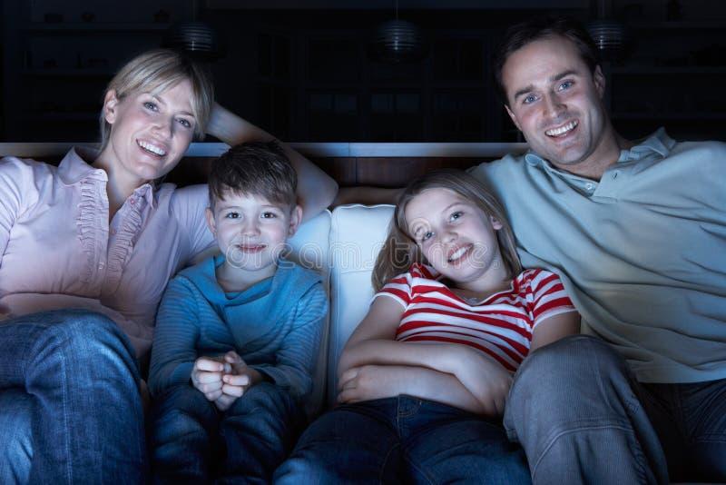 Família que presta atenção à tevê no sofá junto fotos de stock