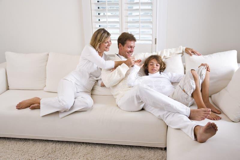 Família que relaxa em casa no sofá branco da sala de visitas fotografia de stock royalty free