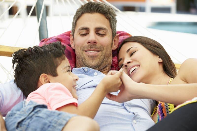 Família que relaxa na rede do jardim junto fotografia de stock royalty free