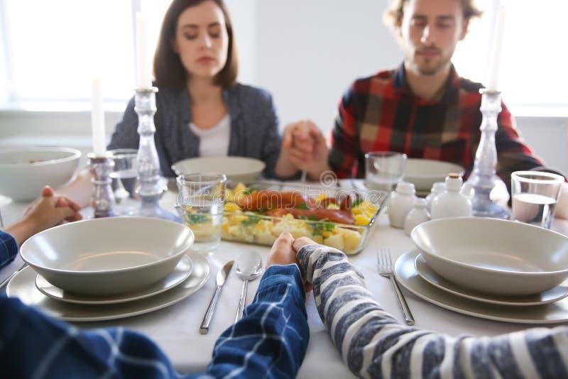 Família que reza antes da refeição em casa imagens de stock royalty free