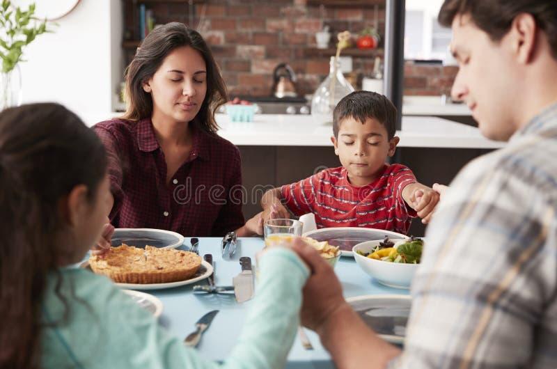 Família que reza antes da refeição em torno da tabela em casa foto de stock