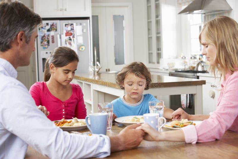 Família que reza antes ter a refeição na cozinha junto foto de stock