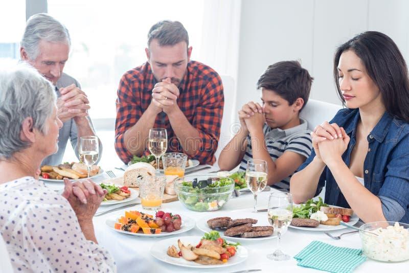 Família que reza junto antes da refeição fotografia de stock