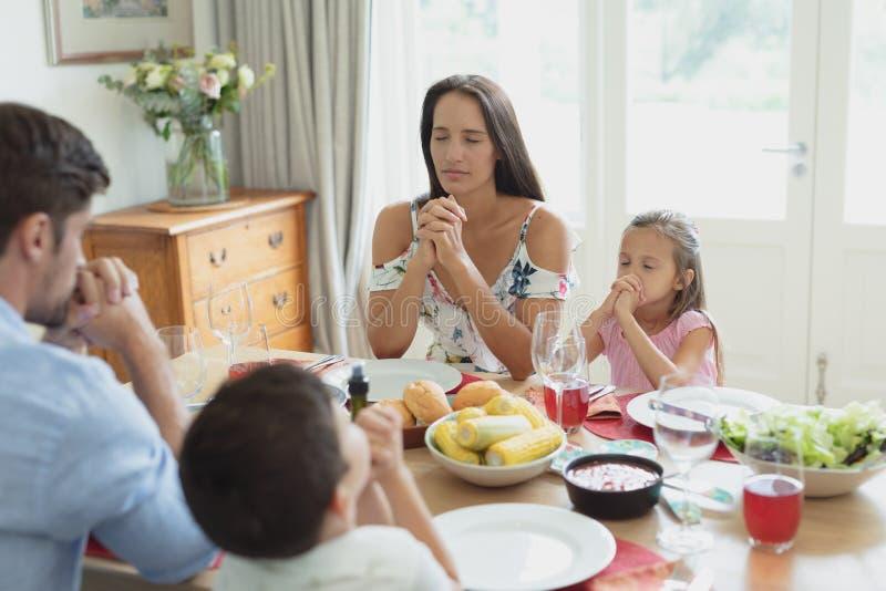 Família que reza junto antes de ter o almoço na mesa de jantar foto de stock royalty free