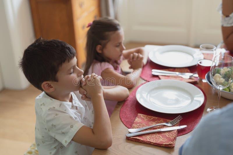 Família que reza junto antes de ter o almoço na mesa de jantar fotos de stock royalty free