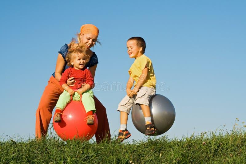 A família que salta na grama foto de stock royalty free