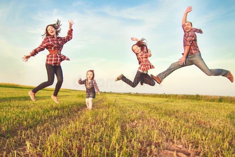 A família que salta no campo foto de stock royalty free