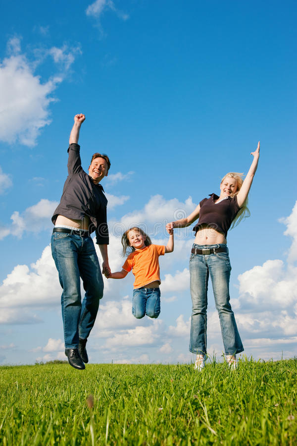 A família que salta no prado no verão imagens de stock royalty free